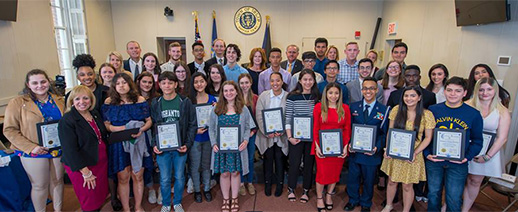 Students stand with their certificates and Town Board