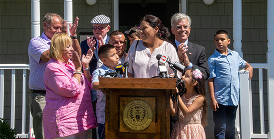 Elected officials stand with the family who received the keys to their new house