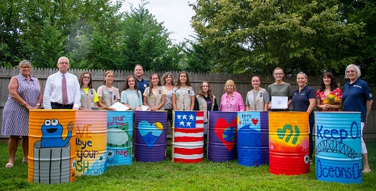 Supervisor Carpenter DPW Commisioner Tom Owens Girl Scout representatives stand beside the girl scouts behind the cans they painted with colorful pictures and murals on them.