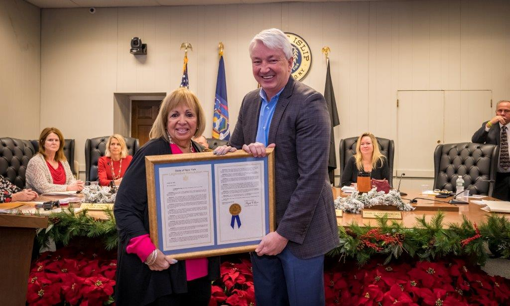 Town Supervisor Angie Carpente stands with NY Senator Phil Boyle, each holding a side of the framed NY resolution commemorating the Town's progress over 335 years.