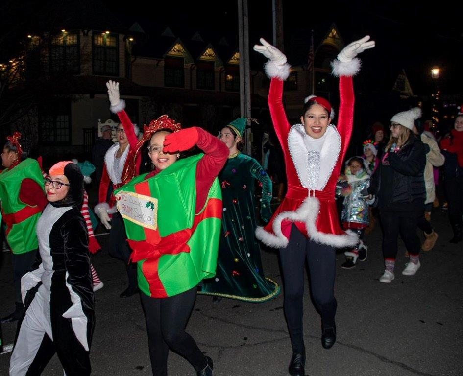 Parade marchers dressed as penguins, presents santa claus and holiday themed icons march down main street.