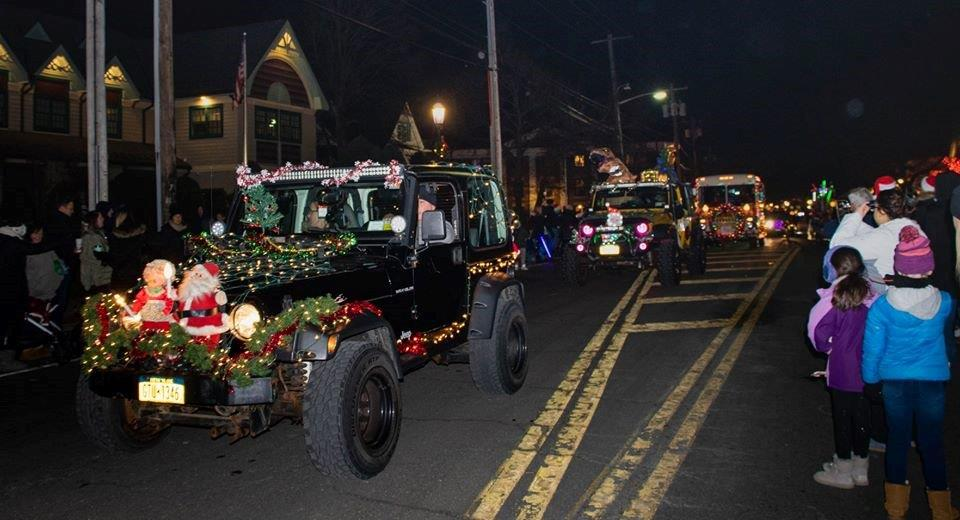 Jeeps and vehicles drive down Main Street in Islip adorned with holiday lights and santa claus themed decorations as residents line the streets on both sides watching the parade.