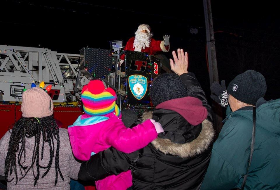Santa Claus waves at the crowd from atop an Islip Fire Engine Truck as 4 residents in the forground and a young girl dressed in pink wave from the side of the road.