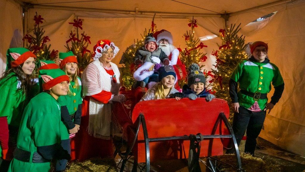 A Santa's Workshop photo backdrop with elves and santa in costume take pictures with event goers.