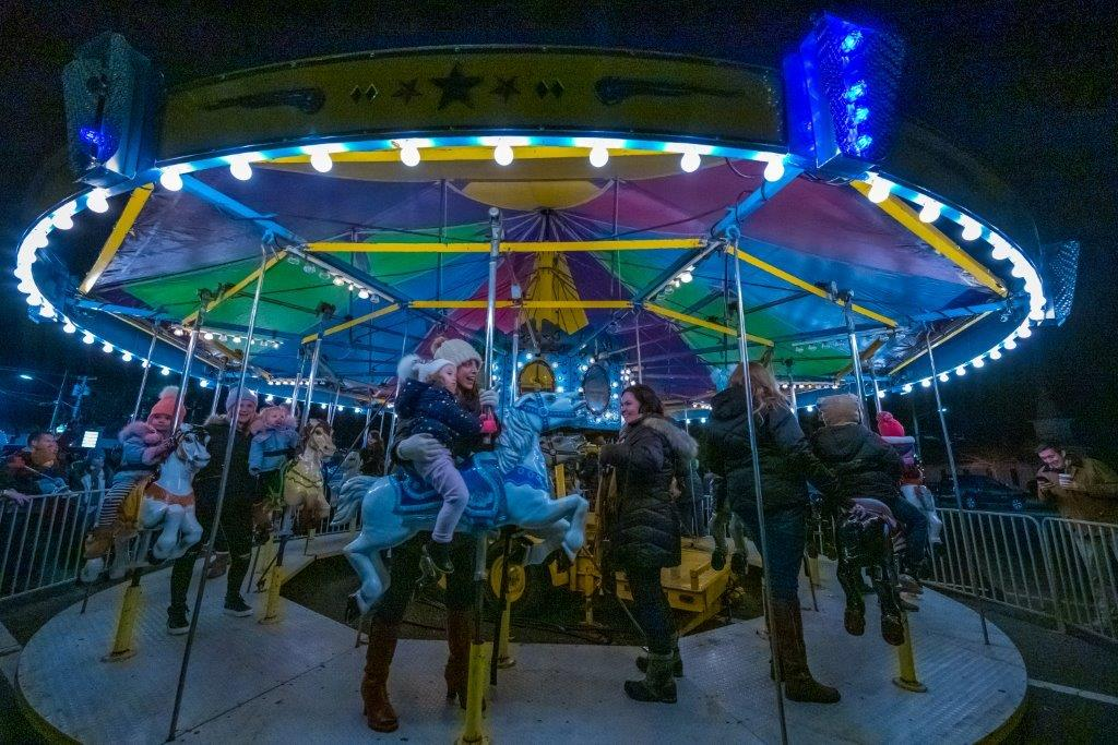 A carousel abright with blue, pink and neon lights circles in action as event goers enjoy the ride.