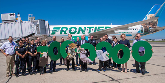 Elected officials, representatives of Frontier and ISP workers pose with a 1,000,000 sign in front of one of frontier's airplanes