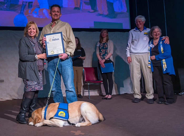 Supervisor Carpenter presents Paul Monfre a citation of honor as he receives his service dog Valor VII