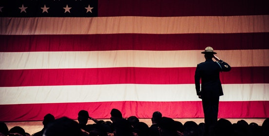 An image of a saluting solider shillouetted against a giant backlit american flag, a shillouetted crowd before him.
