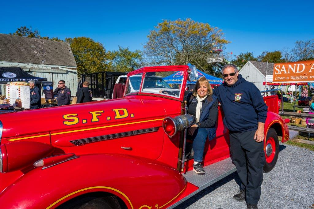 Supervisor Carpenter sits on a vintage Sayville Fire Department Vehicle parked in the middle of the festival.