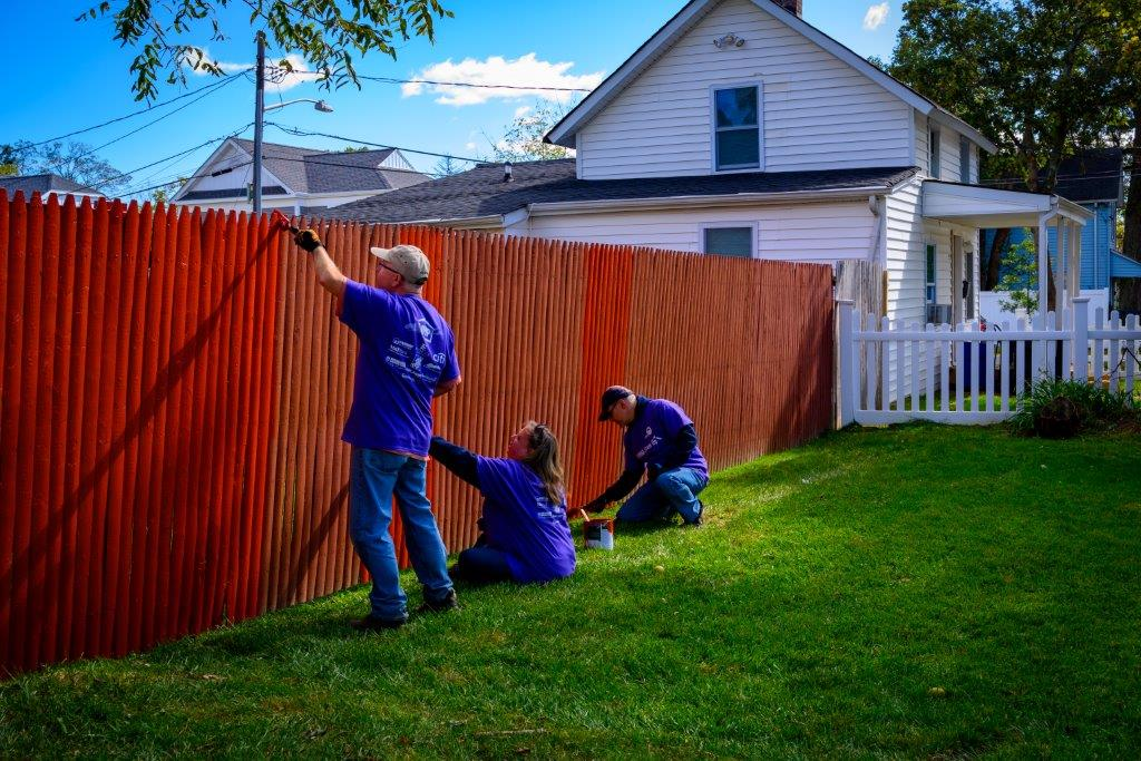 volunteers paint a fresh new fence over green lawns, blue skies and a clean looking property