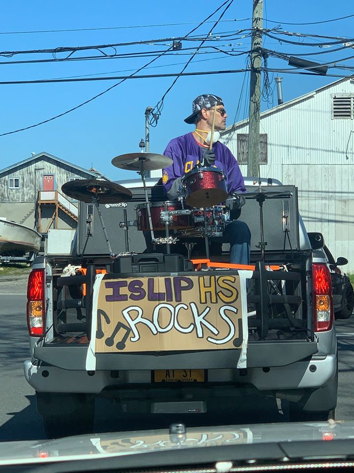 Islip HS Rocks a sign says on the back of a pickup with drummer in bed