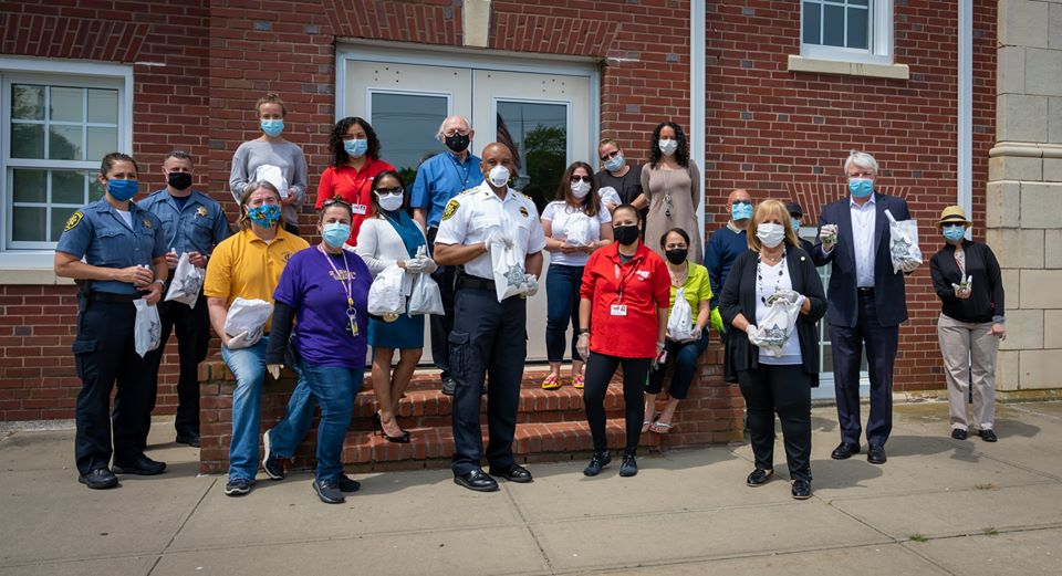 local officials stand in socially distanced group with the produced PPE