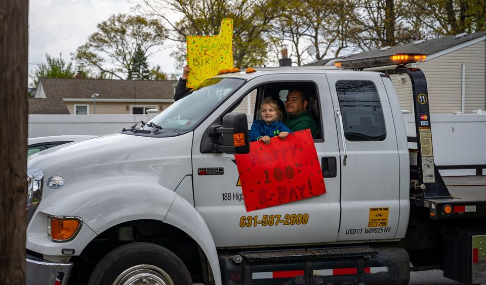 Father and young daughter lean out of truck holding brithday sign
