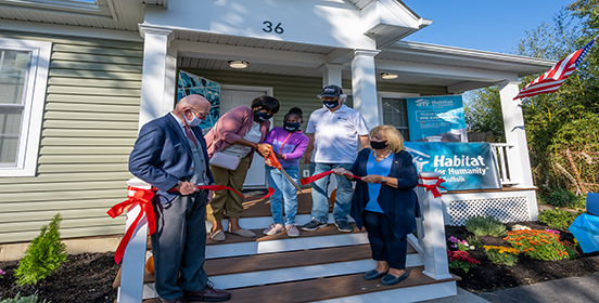 Supervisor Angie Carpenter stands with the Williams family and Habitat for Humanity at the ribbon cutting for their new home.