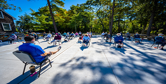 Fitness Instructor, Nick is sitting in a chair facing a group of senior citizens, the group is extending out their leg as part of the workout routine
