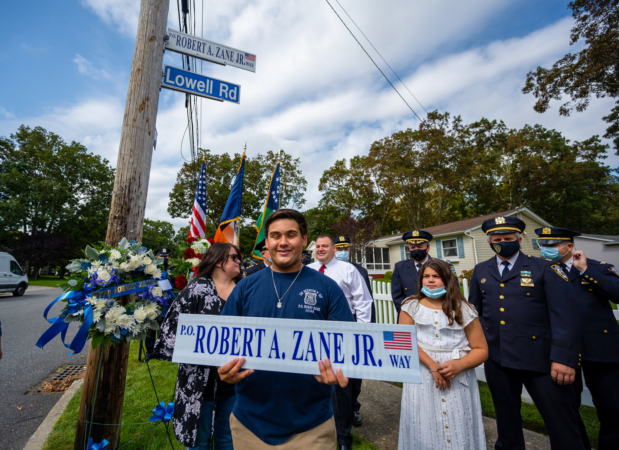 Robert's Son, proudly holds the street sign with his dad's name