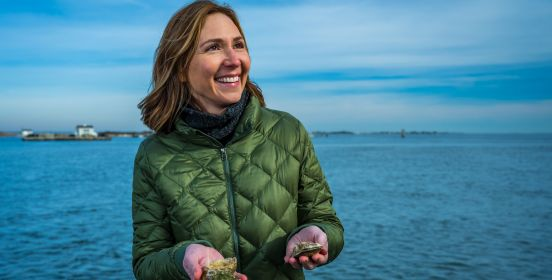 Aileen holds up 2 oysters in her hands while smiling and looking off to camera right, the blue calm waters of the bay rolling behind her.