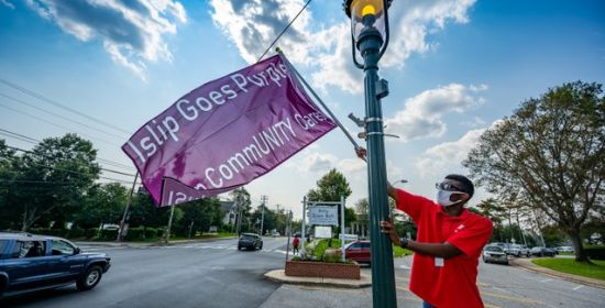 man hangs Islip Goes Purple sign from light post