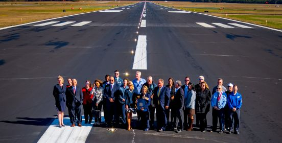 Supervisor Carpenter, Councilman Cochrane, Councilwoman Mullen and members of ISP staff stand on the new runway as a high up shot takes a picture below, the new runway narrowing into the vanishing point behind them.