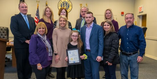 Supervisor Carpenter and the Islip Town Board stand with Ava in the Town Board, having just awarded her for her efforts.