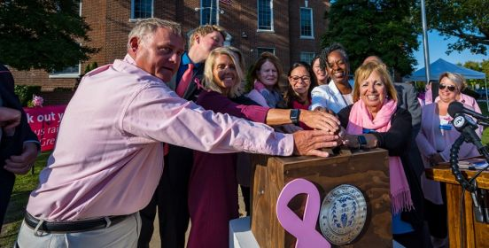 Town Supervisor Angie Carpenter, members of the Islip Town Board place their hands on the lever ready to light the coupola above town hall pink for the month of October.