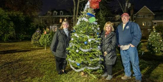 Supervisor Carpenter stands with DPW personnel beside a decorated tree with beautifully adorned trees in the distance behind her along the lawn of Brookwood Hall, seen majestic in the background.