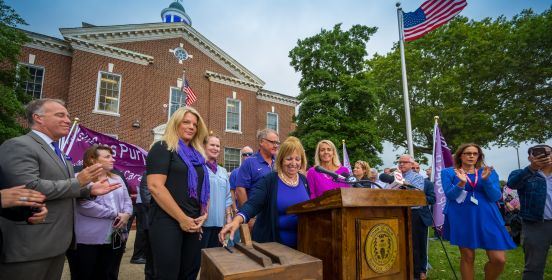 Islip Supervisor, the Islip Town Board, and local officials stand outside the Town Hall building at a podium surroiunded by a crowd as the coupola atop the Town Hall building is illuminated purple