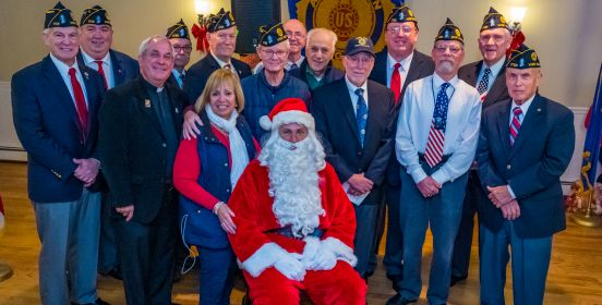 Town Supervisor Angie Carpenter poses for a photo with American Legion members and Santa in the center.