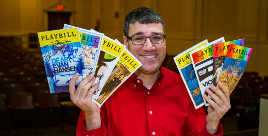 Brian seated in the 401 auditorium holding up an array of playbills, rows of seats in the background behind him.