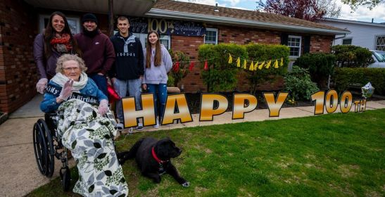 Ehtel, her dog, and her family all pose for a group photo with happy 100 written across her lawn