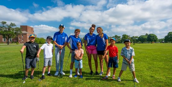 Instructors and kid golfers pose for a photo leaning on clubs over brilliant green fairway and bright blue and cloud speckled skies.