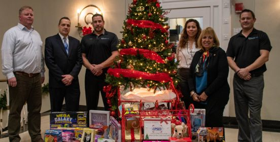 Supervisor Carpenter, Youth Bureau Executive Director Tim Mare and representatives from UPSEU pose for a photo beside the Town Hall Rotunda Tree with toys spilling from under its brances.