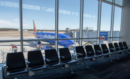 An image of a row of seats in front of terminal glass, a southwest airplane at the terminal on the other side.