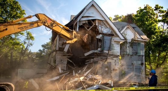 An image capturing the moment the excavator smashes into the zombie house with water from the spray control hoses catching in the morning sun, creating wispy pillars of sunbeams under blue skies.