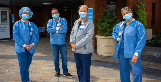 4 Nurses in PPE post in front of hospital