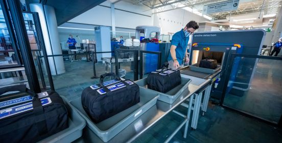 bags wait on conveyor belt for scanner