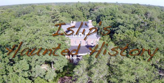 "A drone shot above the treeline with Brookwood Hall peaking through in the clearing, the words ""Islip's Haunted History"" written on screen in brown text."