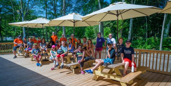 Camp kids line the deck of the new facilities under brand new picnic tables and umbrellas.