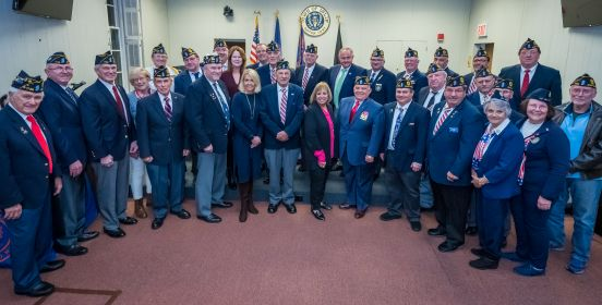 Supervisor Carpenter, the Islip Town Board, and all honored veterans stand in a ring infront of the town board room, posing for a large group photo.