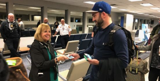 Town Supervisor Angie Carpenter hands a passenger his boarding pass