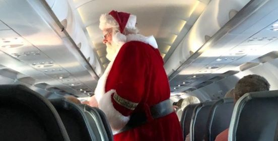 A very official looking Santa walks the isles of the flight.