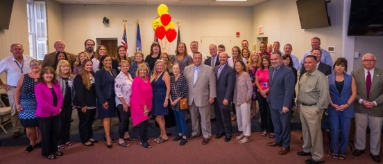 Islip Supervisor Angie Carpenter, members of the Islip Town Board, Food for Hope, and Town of Islip staff pose in the town board room, red and yellow Food for Hope balloons behind them.