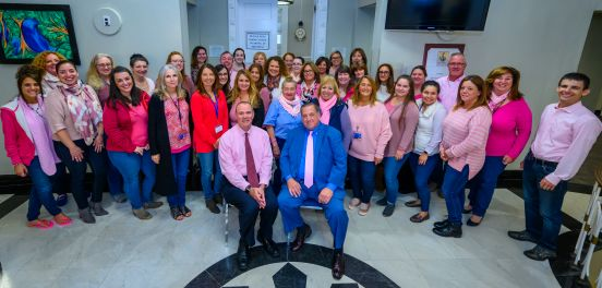 Town Supervisor Angie Carpenter, members of the Islip Town Board, as well as many members of TOI staff and employees, pose for a photo outside the Town Board room, wearing their pink in support of the cause.