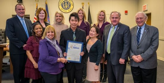 Supervisor Carpenter and the Islip Town Board pose for a photo with Kevin and his family, honoring him for his historic academic achievements.