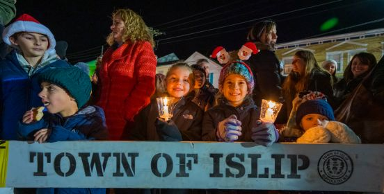 Children with smiles and a lit candle look on at the camera above a wooden horse barrier with the words Town of Islip printed on it.