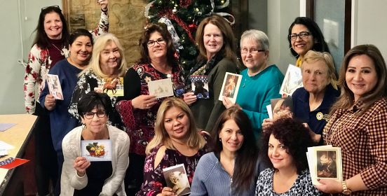 Town Clerk Olga Murray and Clerk's Office staff pose for a group photo holding seasonal greetings cards.