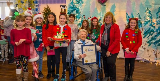 Supervisor Carpenter poses for a photo with Rose Santoro   who turned 101 surrounded by students of Sycamore Avenue   Elementary School who came to sing Christmas carols.