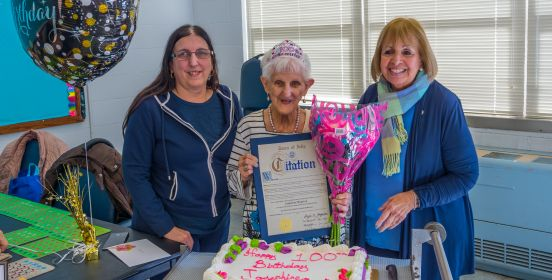 The centenarian stands above her Birthday cake along side Supervisor Carpenter, holding a Town Citation of Recognition and a bouquet of flowers.