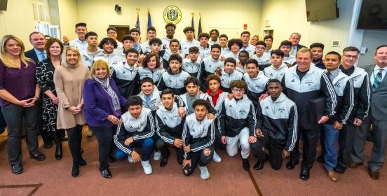 An image of Islip Town Board and Brentwood Boys Soccer Team all squeezed into the Town Board Room for a large group photo.