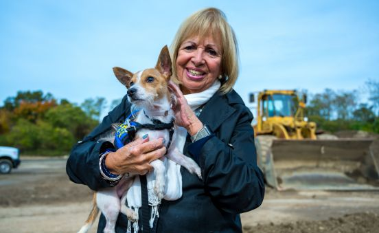 Islip Supervisor Angie Carpenter poses for a photo holding a small pupper, infront of the broken ground where the future shelter will be, a bulldozer in the background.